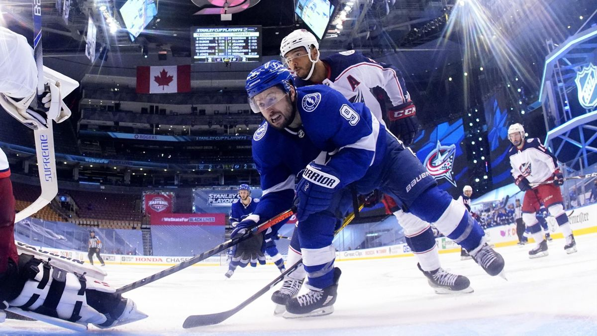Tyler Johnson #9 of the Tampa Bay Lightning reaches for the puck in front of Seth Jones #3 of the Columbus Blue Jackets during the first overtime of Game One of the Eastern Conference First Round of the 2020 NHL Stanley Cup Playoff at Scotiabank Arena on