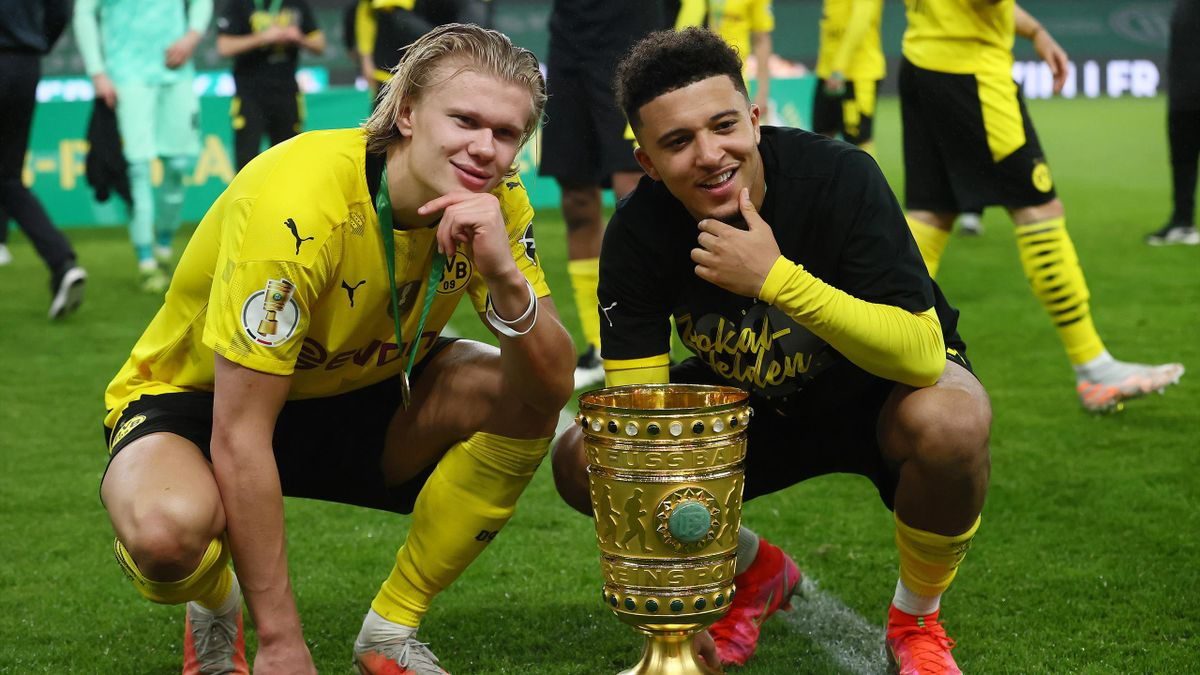 Erling Haaland (L) and Jadon Sancho of Borussia Dortmund pose with the trophy after winning the DFB Cup final match between RB Leipzig and Borussia Dortmund at Olympic Stadium on May 13, 2021 in Berlin, Germany.
