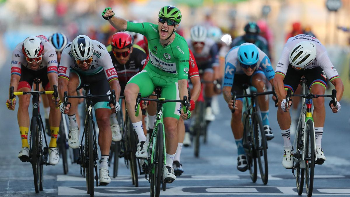 Stage winner Team Deceuninck rider Ireland's Sam Bennett wearing the best sprinter's green jersey celebrates as he crosses the finish line during the 21st and last stage of the 107th edition of the Tour de France