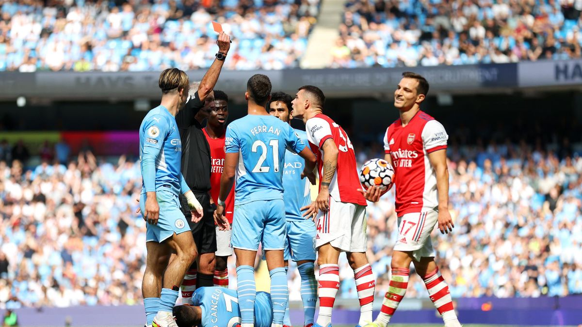 MANCHESTER, ENGLAND - AUGUST 28: Referee Martin Atkinson awards Granit Xhaka of Arsenal a red card during the Premier League match between Manchester City and Arsenal at Etihad Stadium on August 28, 2021 in Manchester, England.