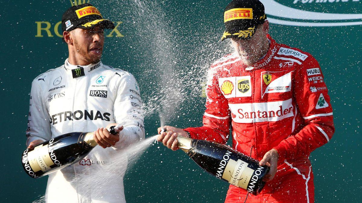 Ferrari driver Sebastian Vettel of Germany (R) sprays champagne alongside second-placed Mercedes driver Lewis Hamilton of Britain