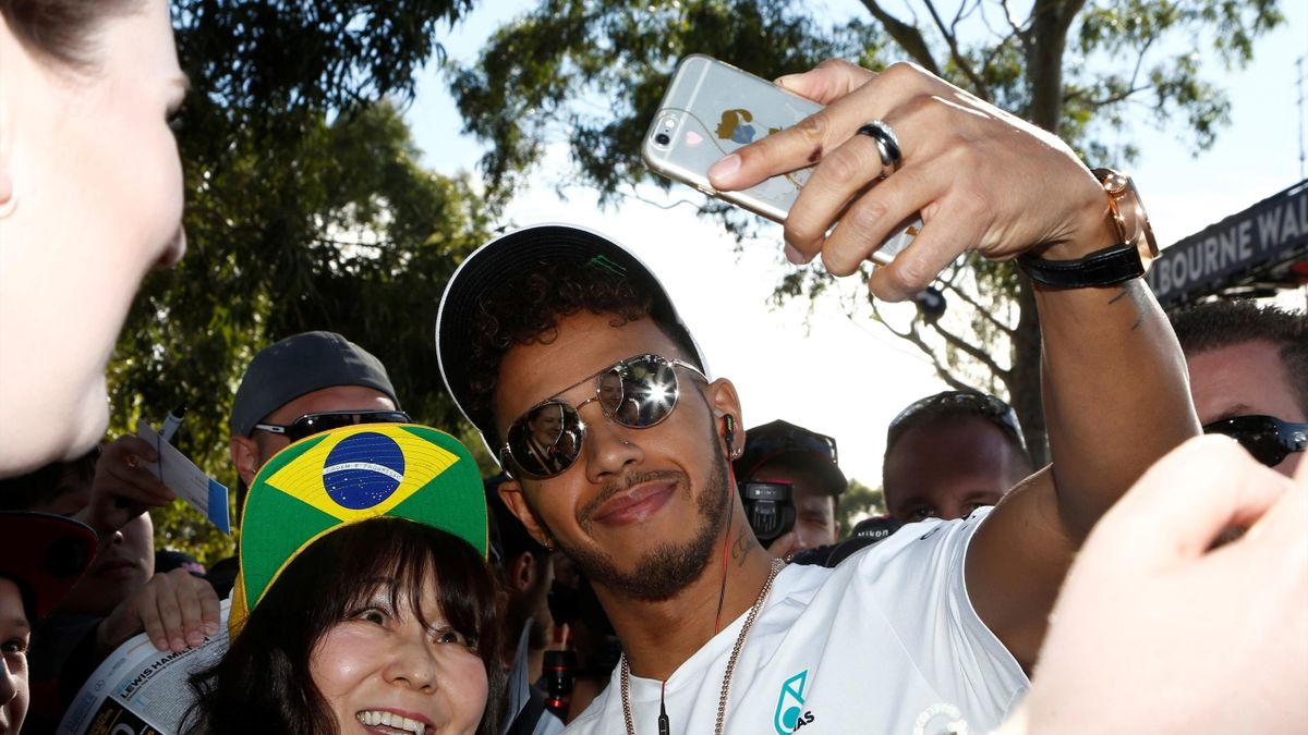 Mercedes driver Lewis Hamilton of Britain takes a selfie with a fan as he arrives at the track.