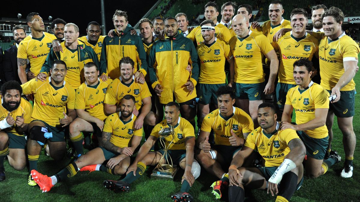 Australian players gather around the trophy after their win in the Rugby Championship match between Australia and Argentina in Perth on September 17, 2016.