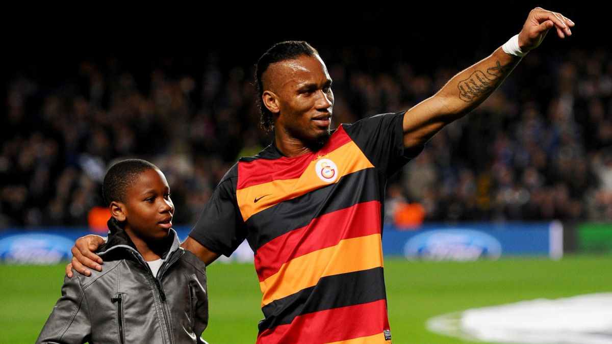 LONDON, ENGLAND - MARCH 18: Former Chelsea player Didier Drogba of Galatasaray and son Isaac wave to the crowd prior to the UEFA Champions League Round of 16 second leg match between Chelsea and Galatasaray AS at Stamford Bridge on March 18, 2014 in Londo