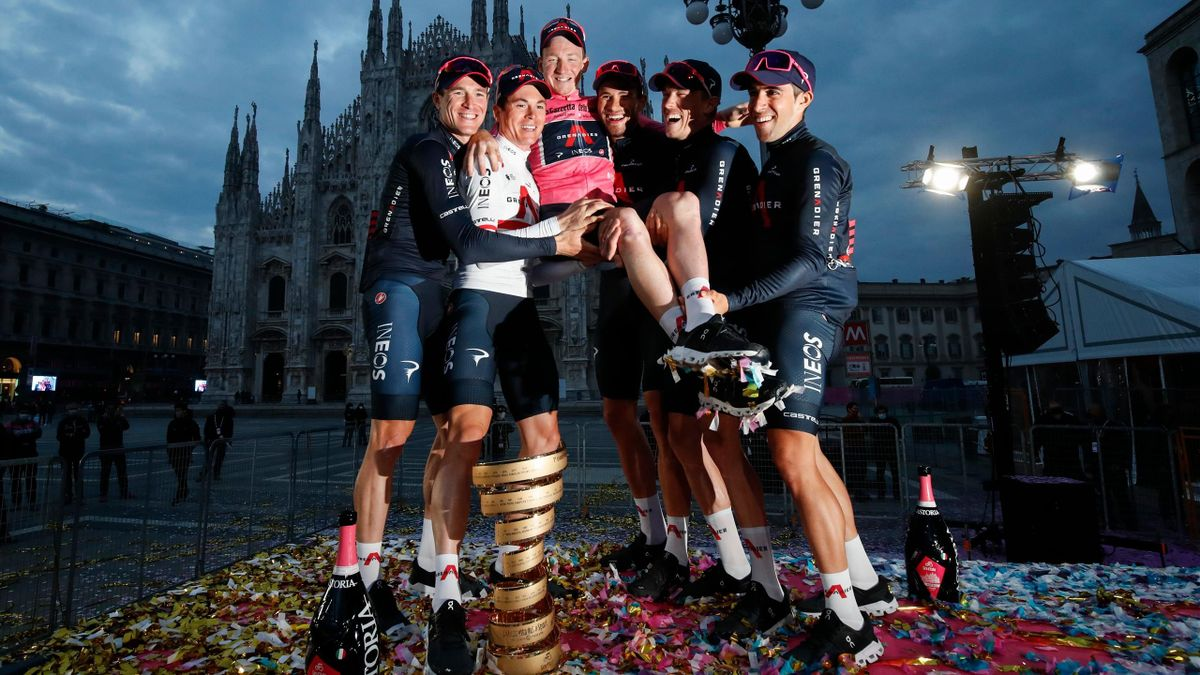 Overall race winner Team Ineos rider Great Britain's Tao Geoghegan Hart wearing the leader's pink jersey celebrates with his teammates in front of the Duomo cathedral, after the the 21st and final stage of the Giro d'Italia 2020