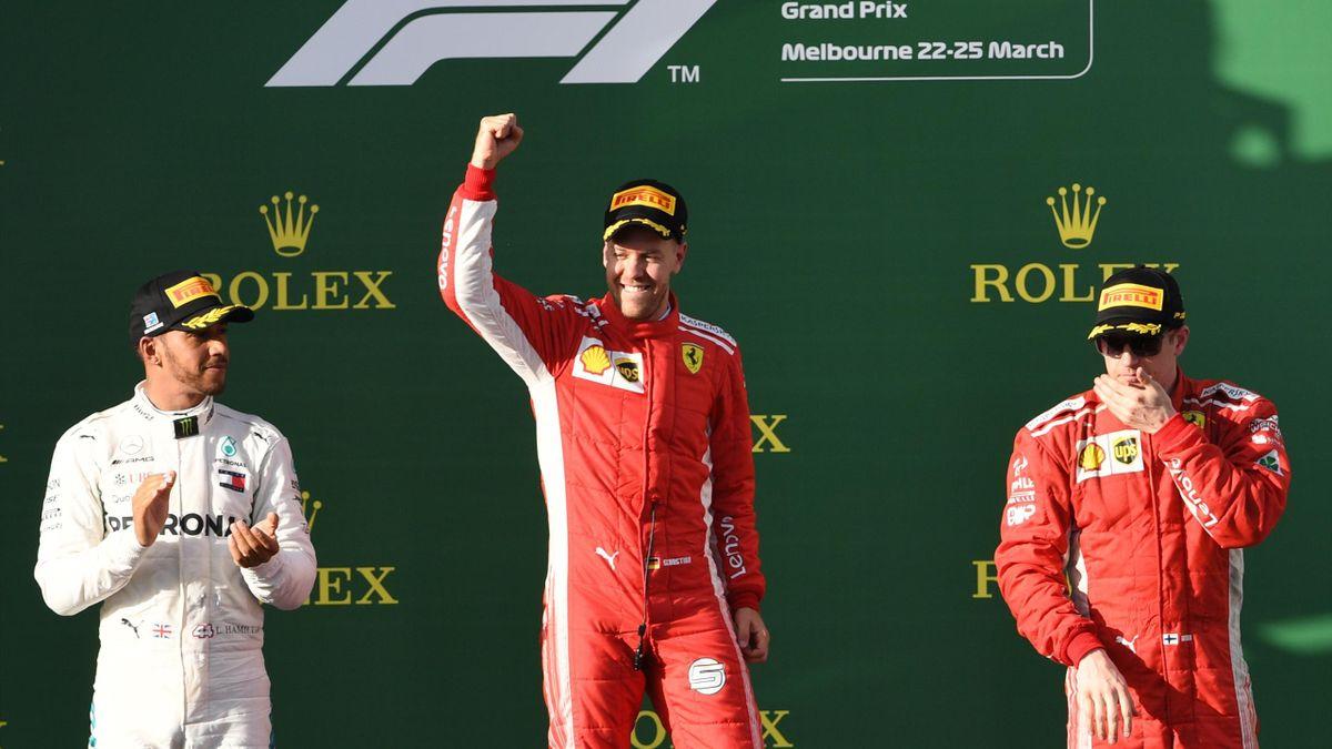 Ferrari's German driver Sebastian Vettel (C) celebrates his victory on the podium next to second-placed Mercedes' British driver Lewis Hamilton (L) and third-placed Ferrari's Finnish driver Kimi Raikkonen (R) after the Formula One Australian Grand Prix in