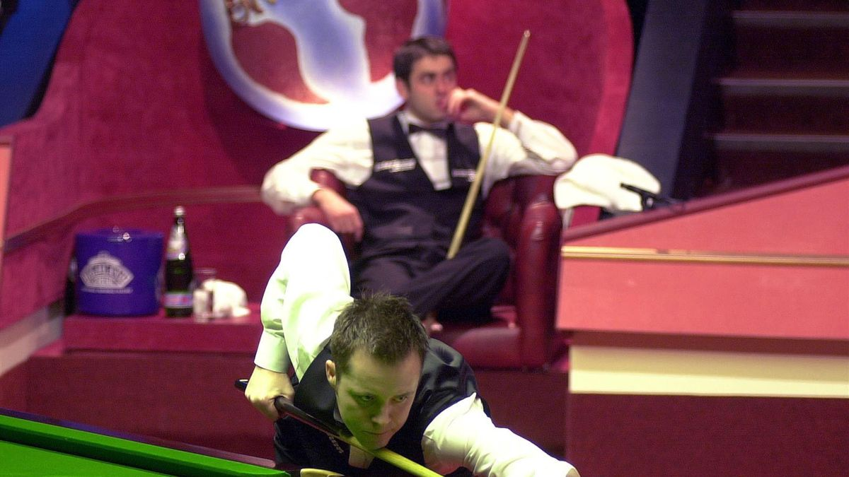 John Higgins of Scotland plays a shot while Ronnie O'sullivan of England