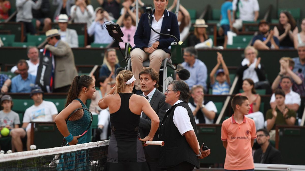 Russia's Darya Kasatkina (L) and Denmark's Caroline Wozniacki (2ndL) speak with officials during their women's singles fourth round match on day eight of The Roland Garros 2018 French Open tennis tournament in Paris on June 3, 2018.