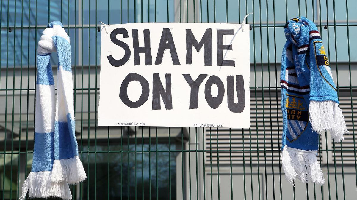 A sign which reads 'Shame On You' is placed between two Manchester City scarves outside the Etihad Stadium