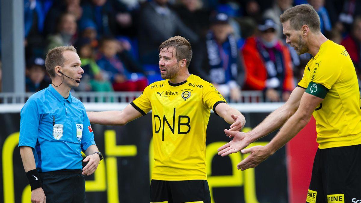 De to tidligere LSK-spillerne Simen Rafn og Frode Kippe i dialog med assistentdommer under en Eliteserie-kamp i 2019.