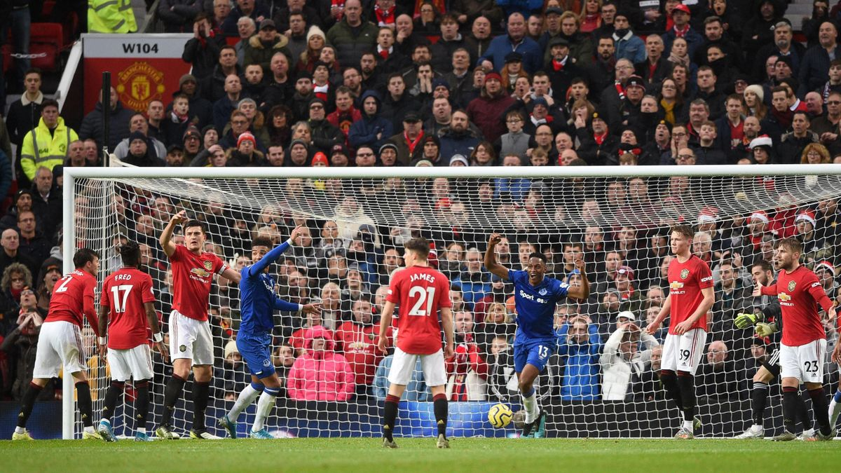 Everton's Colombian defender Yerry Mina (3R) reacts after Manchester United's Swedish defender Victor Lindelof (L) scored an own goal for Everton's first goal during the English Premier League football match between Manchester United and Everton at Old Tr