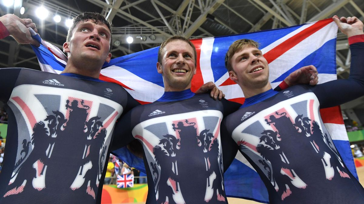 Britain's Callum Skinner, Britain's Jason Kenny and Britain's Philip Hindes hold up a British flag as they celebrate after winning gold in the men's Team Sprint track cycling finals at the Velodrome during the Rio 2016 Olympic Games in Rio de Janeiro on