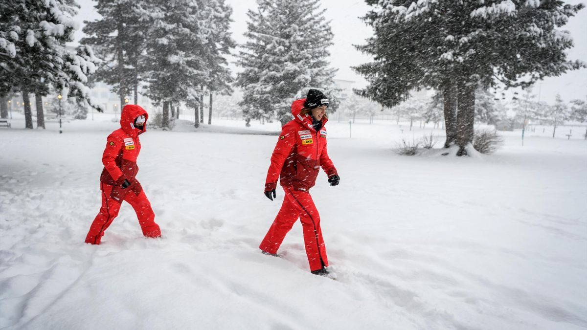 Swiss ski racers Lara Gut-Behrami (L) and Michelle Gisin leave under heavy snow after a press conference on the eve of their Women's Super G race at the FIS Alpine Ski World Cup, in St. Moritz