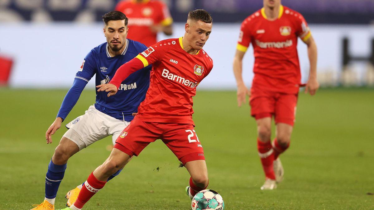 Florian Wirtz von Bayer Leverkusen (vorne) im Zweikampf mit Suat Serdar (FC Schalke 04)