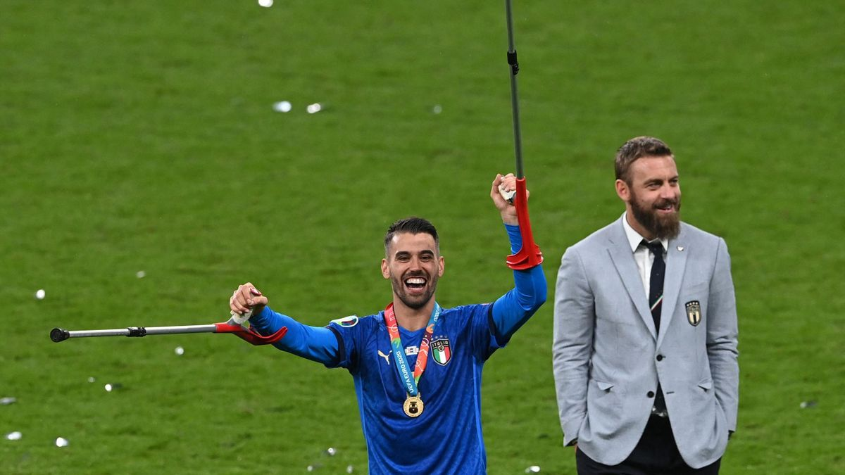 Italy's defender Leonardo Spinazzola (L) and assistant coach Daniele De Rossi walk on the pitch after winning the European Championship trophy after Italy won the UEFA EURO 2020