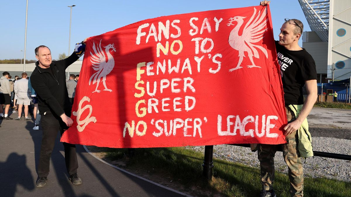 Fans hold up a protest banner against Liverpool FC and the European Super League outside the stadium