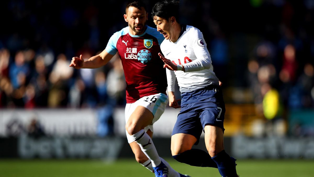 Heung-Min Son of Tottenham Hotspur (R) is challenged by Phillip Bardsley of Burnley during the Premier League match between Burnley FC and Tottenham Hotspur at Turf Moor on February 23, 2019 in Burnley, United Kingdom.