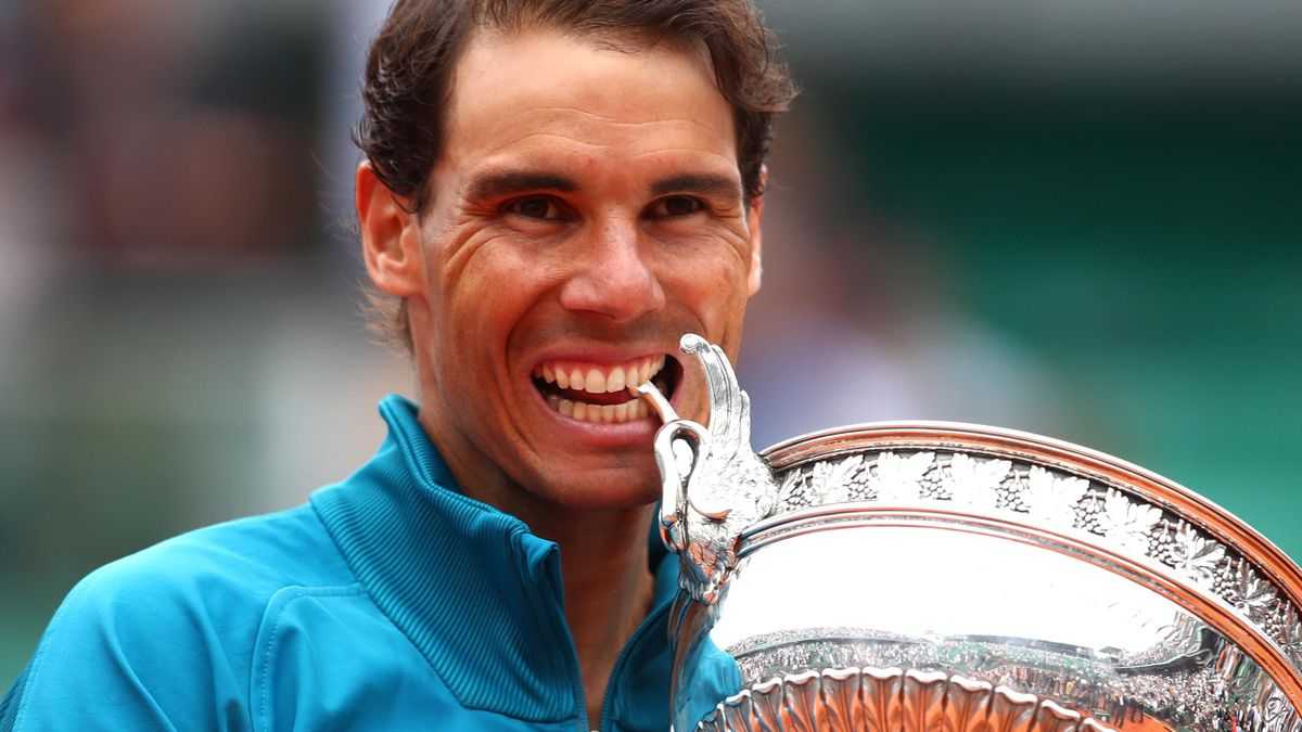 Rafael Nadal of Spain bites the Musketeers' Cup as he celebrates victory following the mens singles final against Dominic Thiem of Austria during day fifteen of the 2018 French Open at Roland Garros on June 10, 2018 in Paris, France