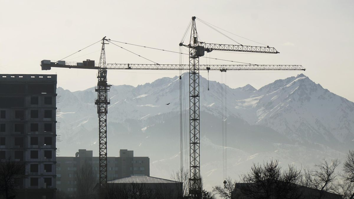 Construction cranes are seen against the backdrop of the Tien Shan mountains in Almaty, Kazakhstan, January 7, 2016.
