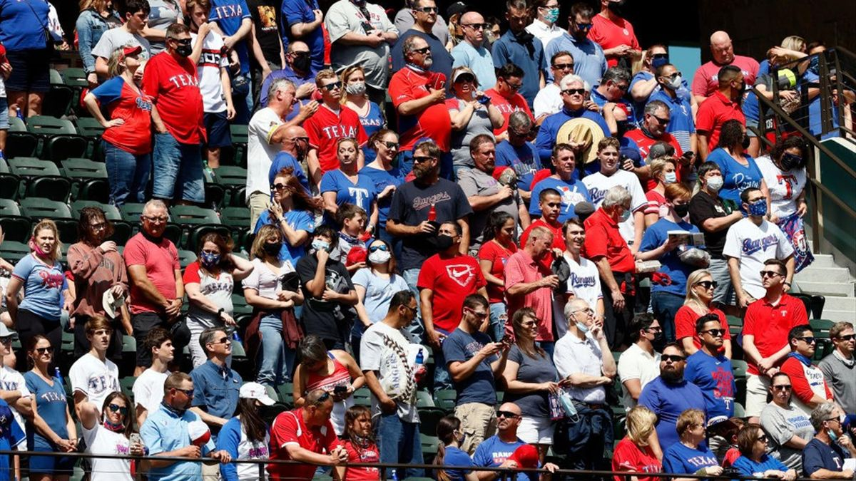Fans scramble for a foul ball in the second inning as the Texas Rangers take on the Toronto Blue Jays on Opening Day at Globe Life Field on April 05, 2021 in Arlington, Texas