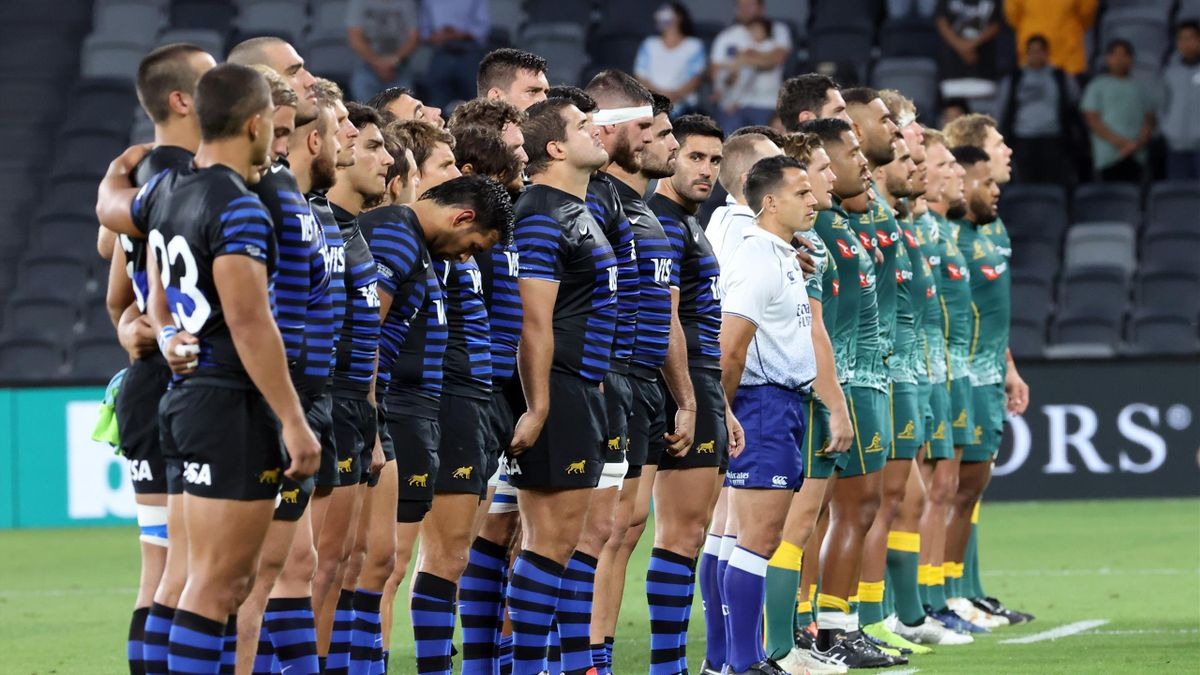 Argentina (L) and Australian players (R) listen national anthems before the 2020 Tri-Nations rugby match between the Australia and Argentina in Sydney on December 5, 2020. (