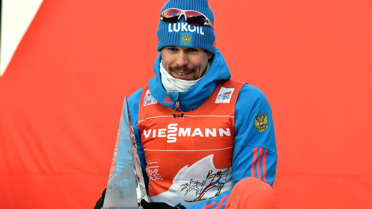 """Winner Russia's Sergey Ustiugov celebrates on the podium after winning the Men's 9 km pursuit free competition of the """"Tour de Ski"""" Cross Country World Cup on January 8, 2017"""