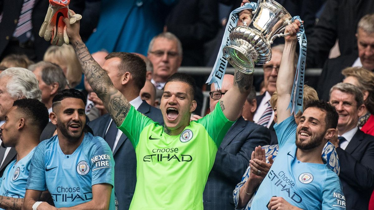 Ederson and Bernardo Silva of Manchester City with FA trophy during the FA Cup Final match between Manchester City and Watford at Wembley Stadium on May 18, 2019 in London, England. (