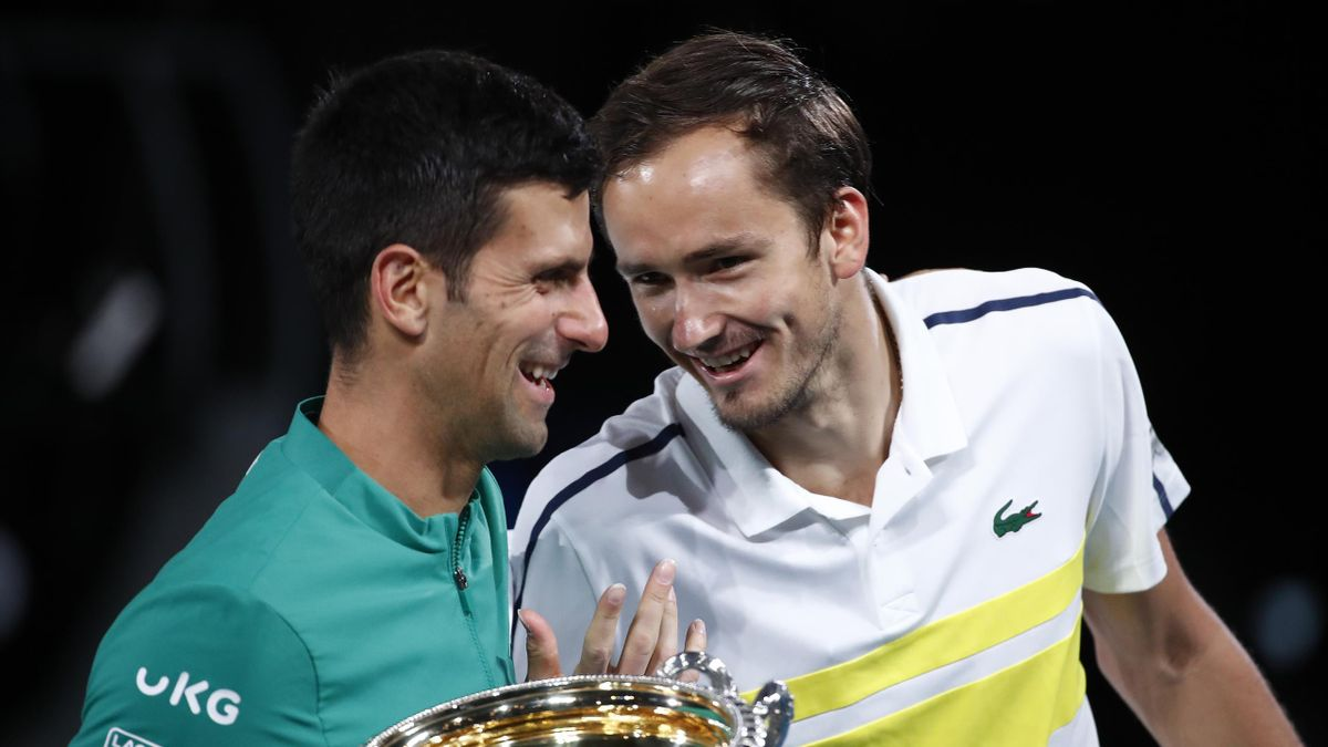 Novak Djokovic of Serbia holds the Norman Brookes Challenge Cup as he shares a joke with opponent Daniil Medvedev of Russia following their Men's Singles Final match during day 14 of the 2021 Australian Open at Melbourne Park