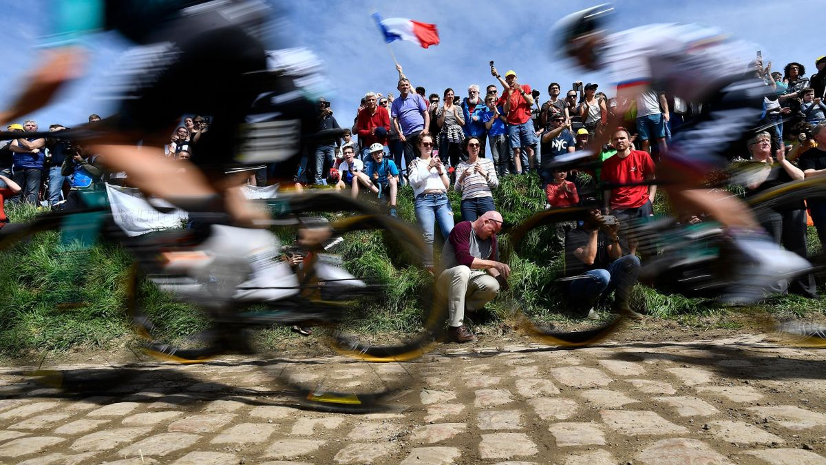 Spectators watch cyclists as they drive across cobbled stone during the 116th edition of the Paris-Roubaix one-day classic cycling race, between Compiegne and Roubaix, on April 8, 2018 in Quievy, northern France