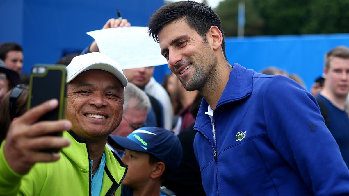 Novak Djokovic poses with a fan for a picture at Eastbourne.