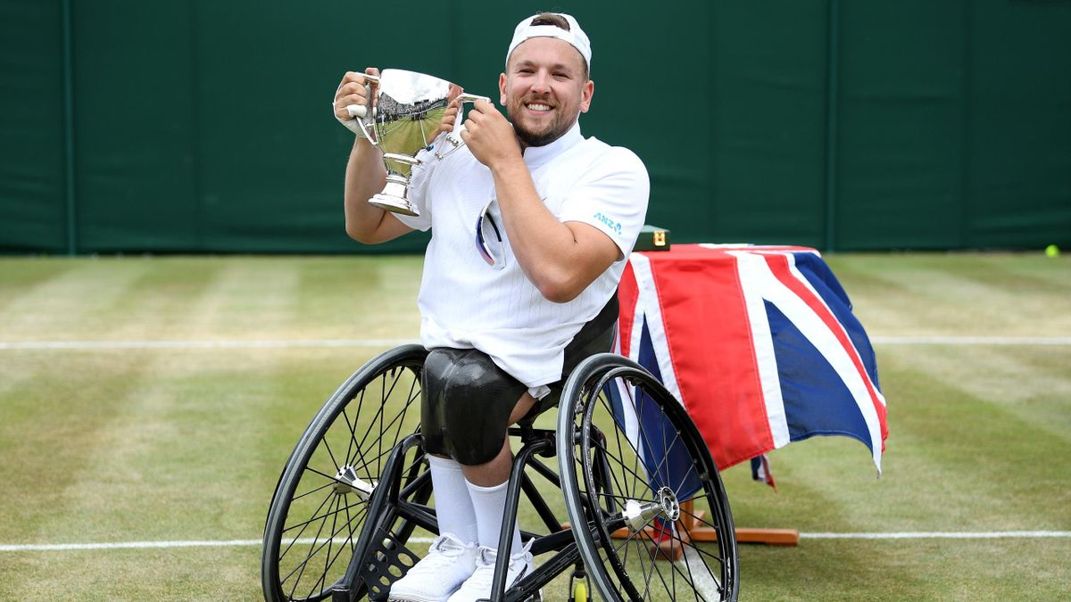 Dylan Alcott of Australia lifts the winners trophy after celebrating victory in the Men's Quad Wheelchair Singles final against Andy Lapthorne of Great Britain during Day twelve of The Championships - Wimbledon 2019