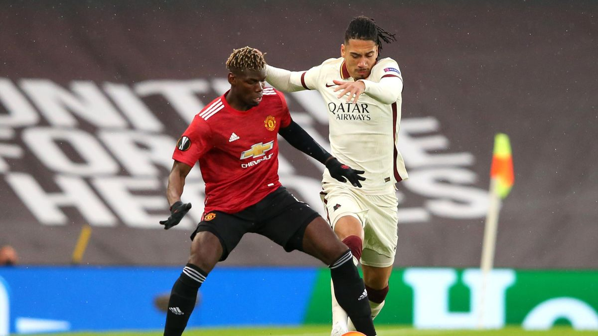 Paul Pogba of Manchester United and Chris Smalling of AS Roma battle for the ball during the UEFA Europa League Semi-final First Leg match between Manchester United and AS Roma at Old Trafford on April 29, 2021 in Manchester, England.
