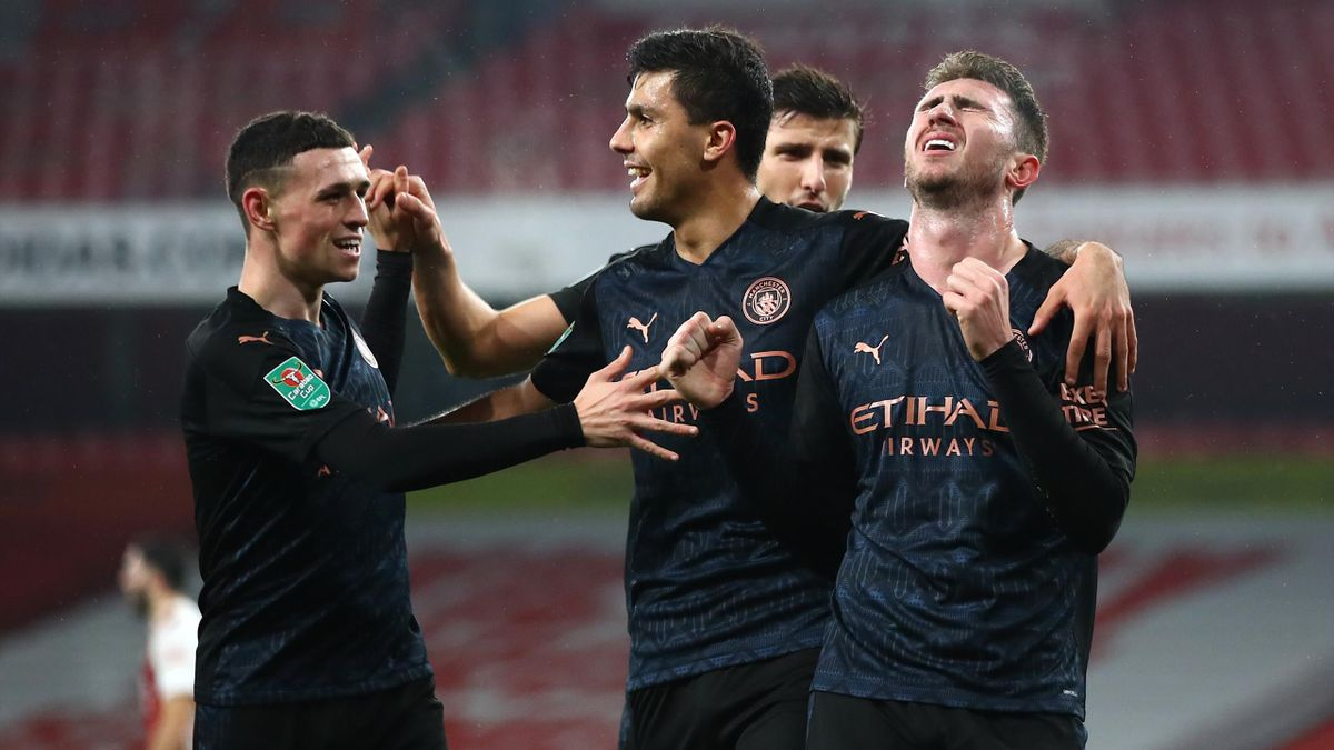 Aymeric Laporte of Manchester City celebrates after scoring their team's fourth goal with teammates Rodri and Phil Foden during the Carabao Cup Quarter Final match between Arsenal and Manchester City