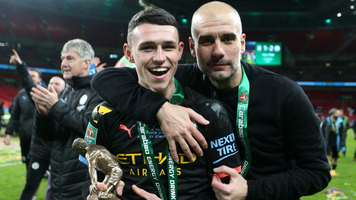 Phil Foden of Manchester City and Pep Guardiola, Manager of Manchester City pose with the trophy following their sides victory during the Carabao Cup Final