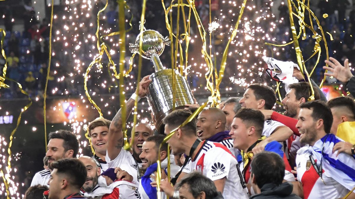Players of River Plate celebrate with the trophy after winning the second leg match of the all-Argentine Copa Libertadores final against Boca Juniors, at the Santiago Bernabeu stadium in Madrid, on December 9, 2018.