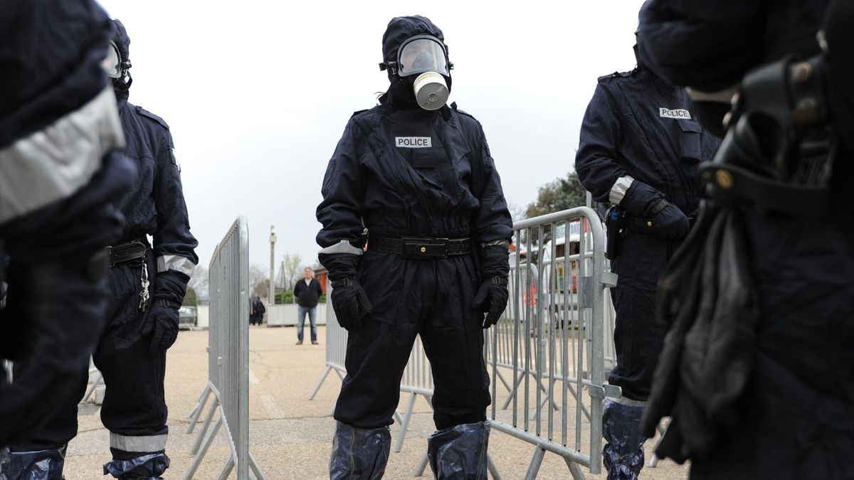 French police officers wear gas masks during a simulation of terrorist attack in football fanzone in Nimes, on March 17,