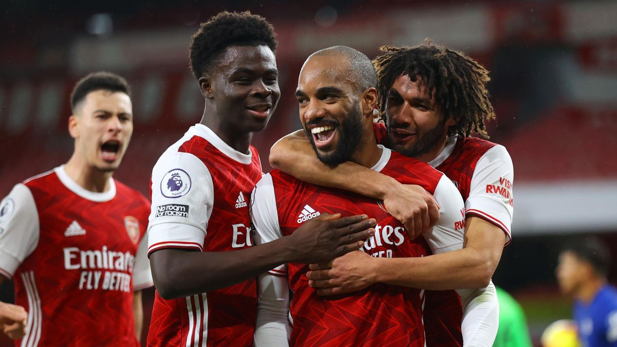 Alexandre Lacazette of Arsenal celebrates with teammates Bukayo Saka and Mohamed Elneny after scoring his team's first goal during the Premier League match between Arsenal and Chelsea at Emirates Stadium