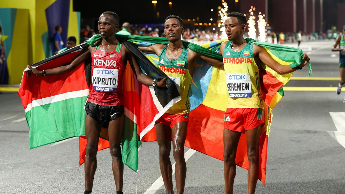 Lelisa Desisa (C) of Ethiopia celebrates with Mosinet Geremew (R) of Ethiopia and Amos Kipruto (L) of Kenya after the Men's Marathon