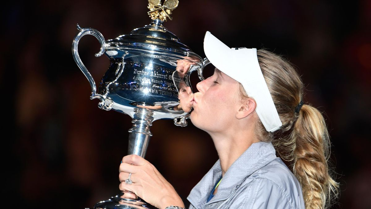 Denmark's Caroline Wozniacki kisses the winner's trophy after beating Romania's Simona Halep