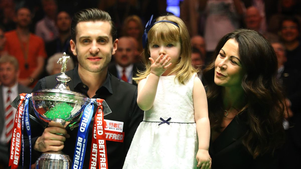 Mark Selby of England poses with the trophy with his duaghter Sofia and wife Vikki after beating John Higgins of Scotland in the final of the World Snooker Championship on day seventeen at Crucible Theatre