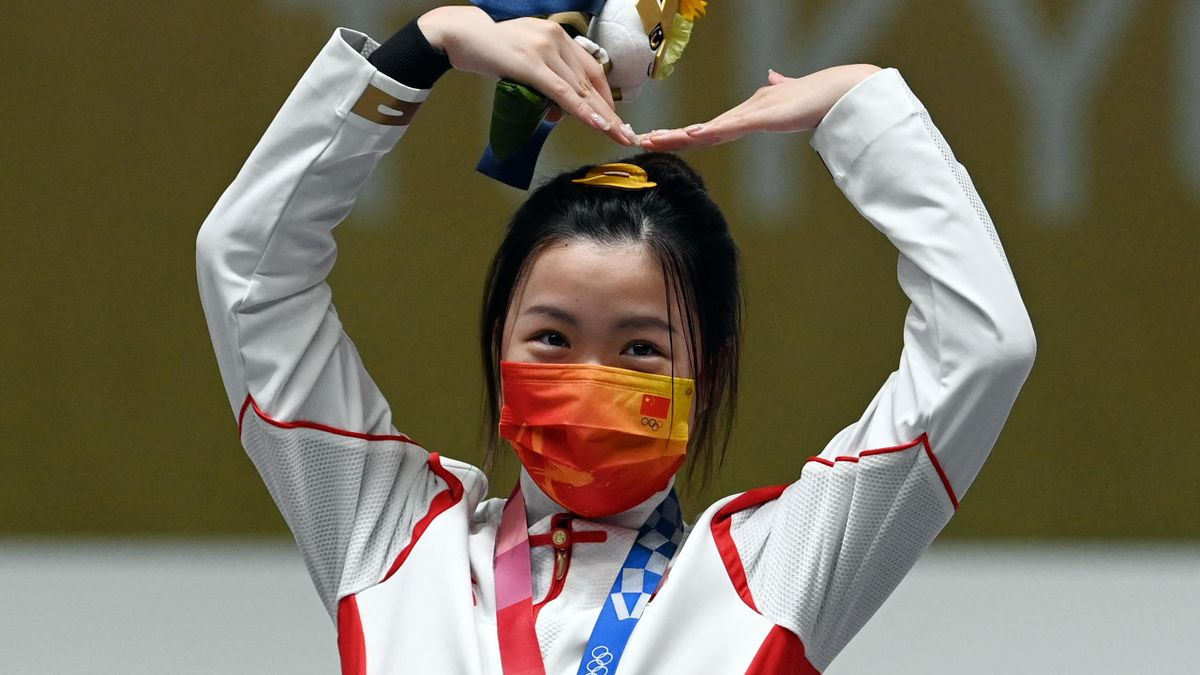 Gold medal winner China's Yang Qian celebrates on the podium after winning the women's 10m air rifle final during the Tokyo 2020 Olympic Games at the Asaka Shooting Range