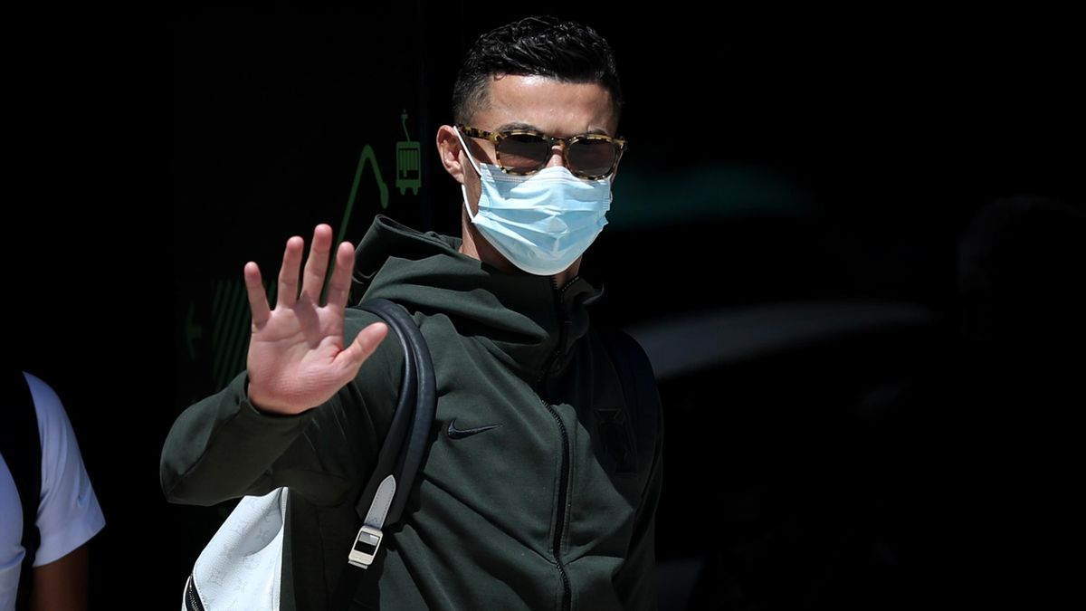Cristiano Ronaldo waves as he arrives at Lisbon airport with teammates on June 28, 2021, after Portugal was eliminated by Belgium