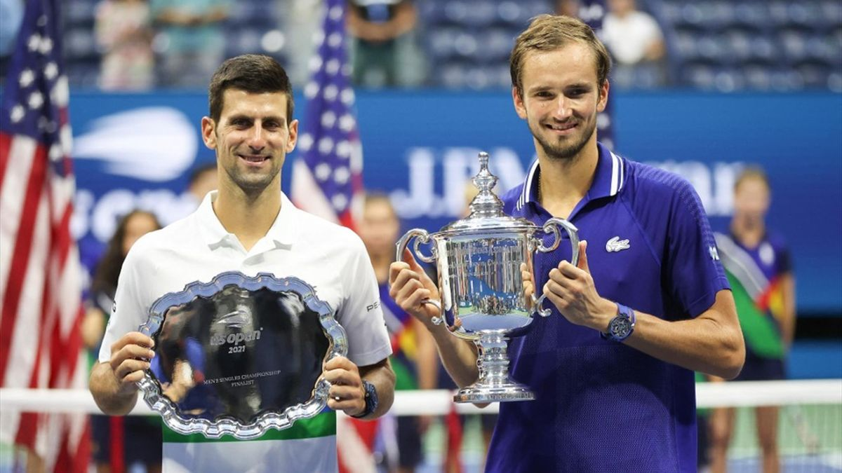 Novak Djokovic of Serbia holds the runner-up trophy alongside Daniil Medvedev of Russia who celebrates with the championship trophy after winning their Men's Singles final match on Day Fourteen of the 2021 US Open at the USTA Billie Jean King National Te