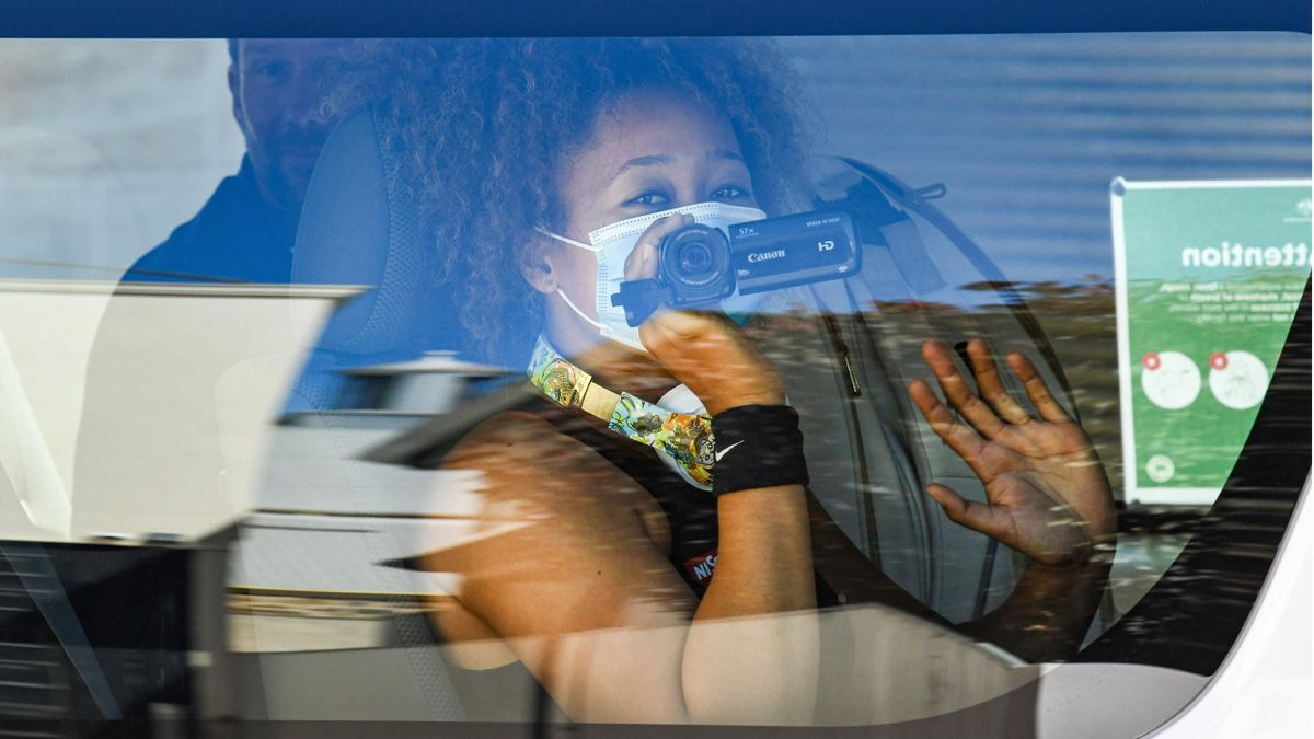 Women's world number three tennis player Naomi Osaka of Japan uses a video camera as she returns with teammates to her hotel after a practice session in Adelaide on January 18, 2021, one of the locations where players have quarantined for two weeks