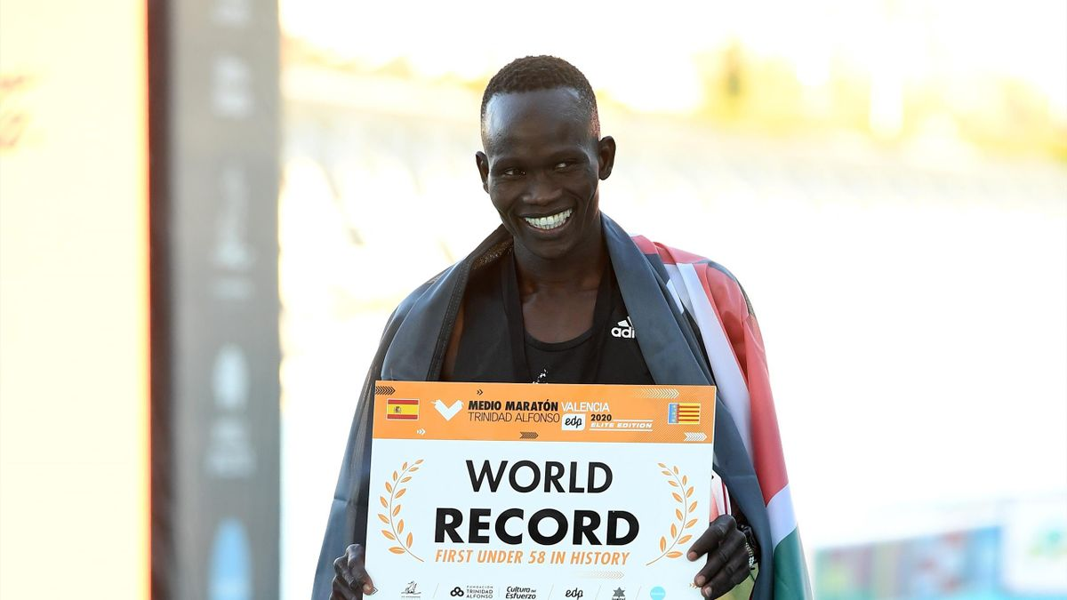 Kibiwott Kandie of Kenya poses as he breaks the Men's Half Marathon World Record wearing the adidas adizero adios pro during the Valencia Marathon