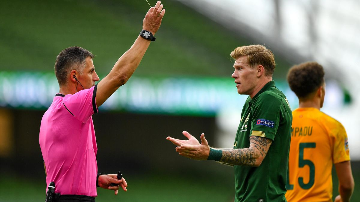 James McClean of Republic of Ireland is shown a yellow card by referee Tasos Sidiropoulos