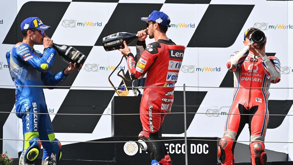 Ducati's Italian rider Andrea Dovizioso (C), second placed Suzuki Ecstar's Spanish rider Joan Mir (L) and third placed Pramac Racing's Australian rider Jack Miller celebrate with champagne on the podium of the Moto GP Austrian Grand Prix at the Red Bull R