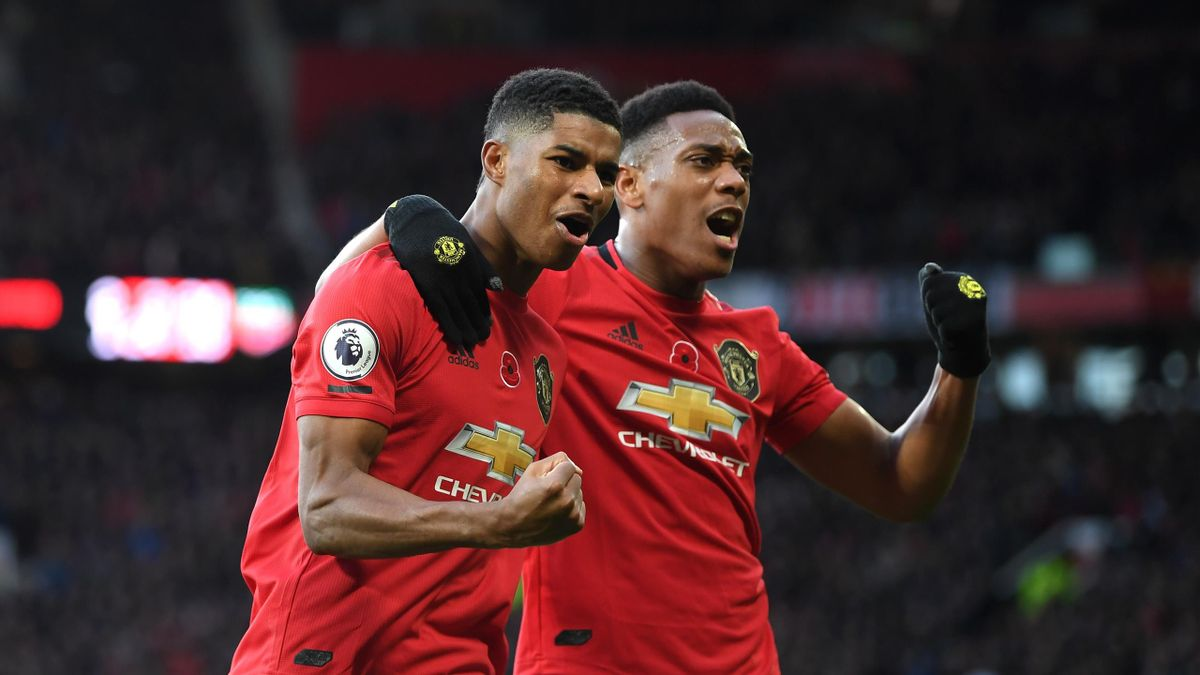 Marcus Rashford of Manchester United celebrates with teammate Anthony Martial after scoring his team's third goal during the Premier League match between Manchester United and Brighton & Hove Albion at Old Trafford on November 10, 2019 in Manchester, Uni