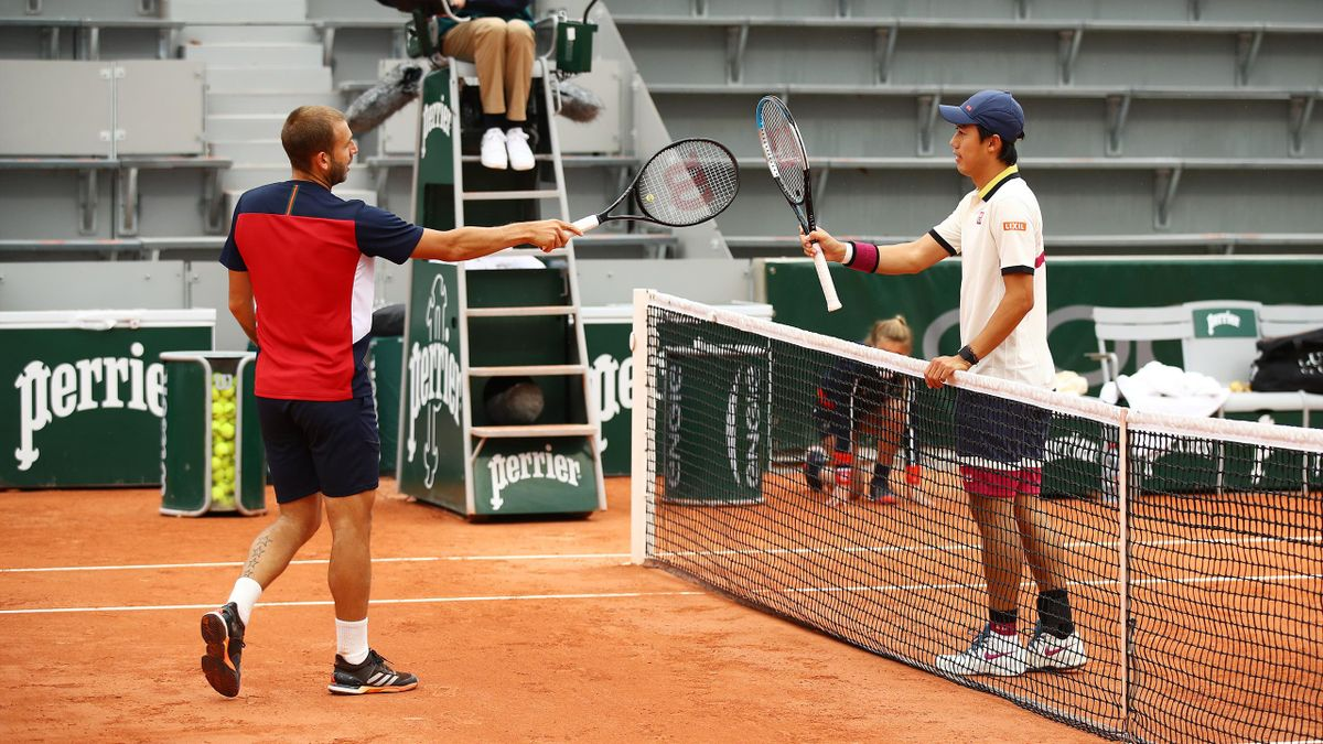 Kei Nishikori of Japan (R) knocks racquets with Daniel Evans of Great Britain as part of COVID-19 precautions after their Men's Singles first round match during day one of the 2020 French Open at Roland Garros