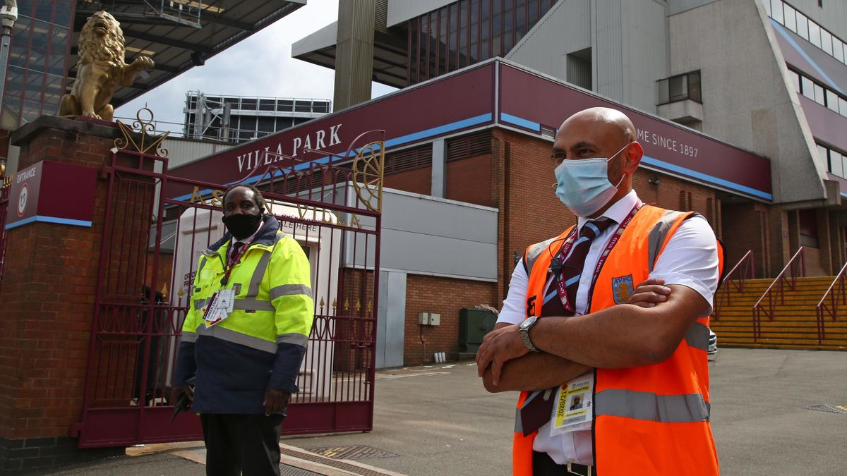 Stewards wearing PPE (personal protective equipment), of a face mask or covering as a precautionary measure against COVID-19, stand outside Villa Park stadium, where the English Premier League football match between Aston Villa and Sheffield United is tak